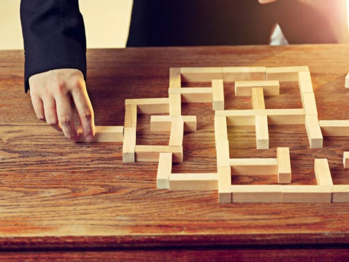 Man and wooden cubes on table. Management and marketing concepts