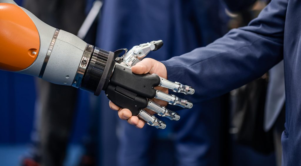 Hand of a businessman shaking hands with a Android robot. The concept of human interaction with artificial intelligence.