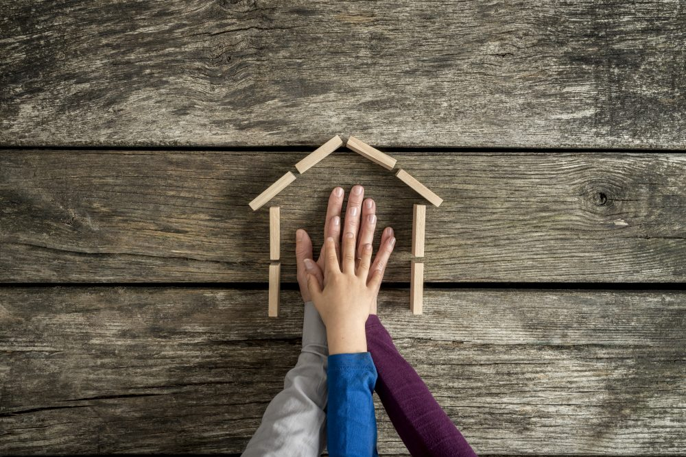Hands of a mother, father and son inside the framework of a house on a rustic wood background with copy space in a conceptual image.