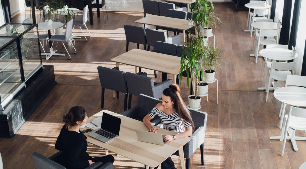 One-on-one meeting.Two young business women sitting at table in cafe. Girl shows colleague information on laptop screen. Girl using smartphone. Teamwork, business meeting. Freelancers working